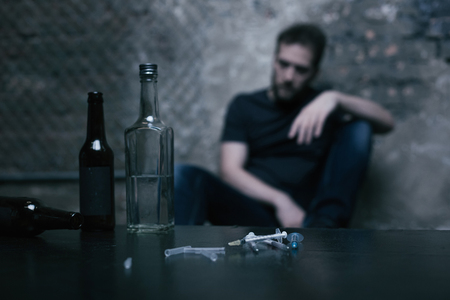 junky: Alcohol in bottles and used syringes lying on the table Stock Photo