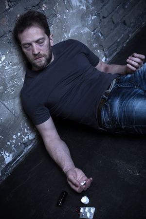 Bearded heroin user suffering from overdose in the dark place