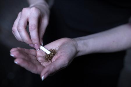 Female drug user holding marijuana cigarette outdoors