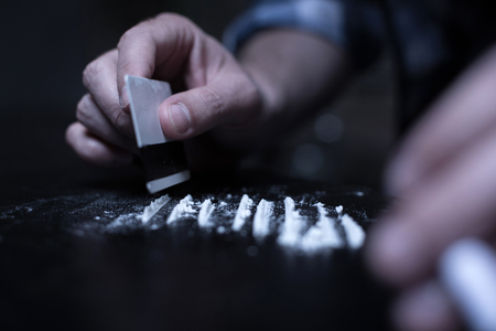 Skillful dope addict preparing cocaine lines in the dark place