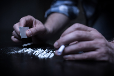 compulsive: Drug addicted preparing heroin lines in the dark place