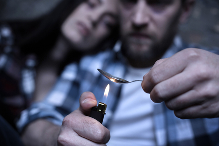 Stoned freaks heating heroin in the spoon outdoors Stock Photo
