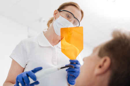 smile close up: Scrupulous qualified dentist using specific tools for whitening