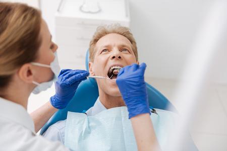 Experienced dentist carefully examining patients cavity