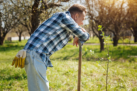 Mature gardener leaning on shovel in backyard Stock Photo