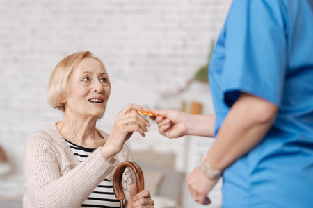 Enchanting trained doctor handing her patient the pills
