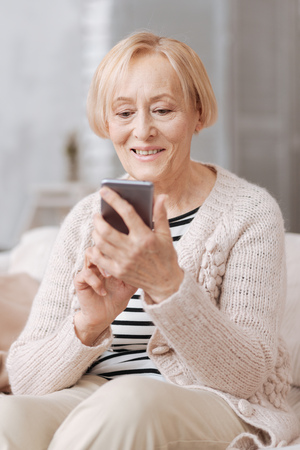 Delighted savvy lady using her gadget Stock Photo