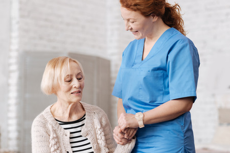 Lovely competent nurse supporting elderly lady Stock Photo