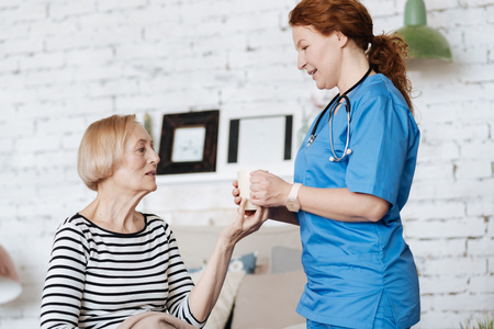 treating: Experienced skillful private doctor treating her elderly patient Stock Photo