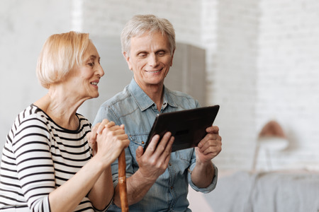 Clever enthusiastic man sharing something with his wife Stock Photo