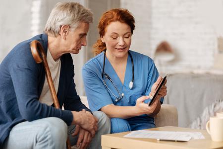 Joyful excited nurse explaining something to her patient