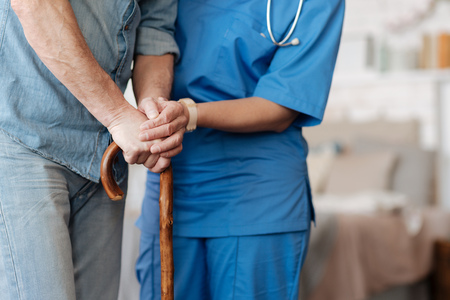 Kind trained nurse helping feeble gentleman walking
