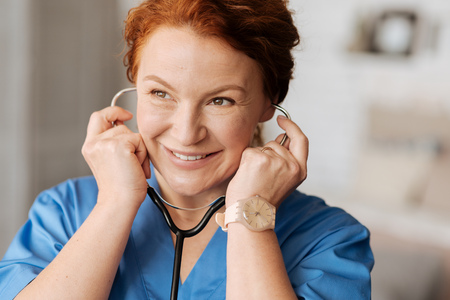 Smiling pleasant doctor using her stethoscope