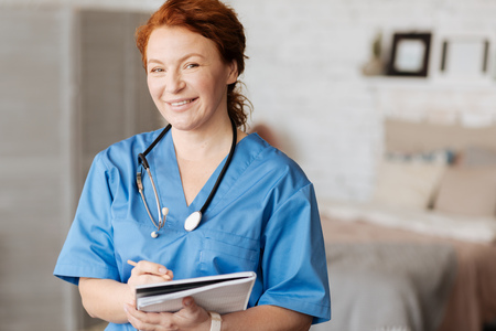 Cheerful excellent doctor holding consultation at home