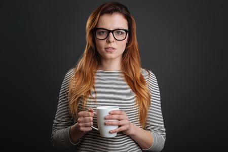 Focused sleepy woman having some coffee Stock Photo