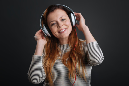 Charmed smiling girl listening to music