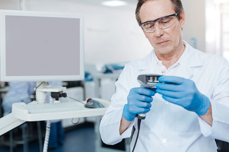 genomics: Very attentive practitioner holding modern technical device
