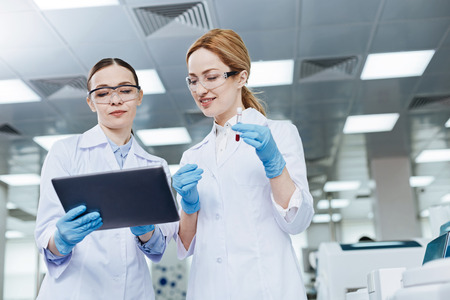 Positive delighted lab assistants looking downwards Stock Photo