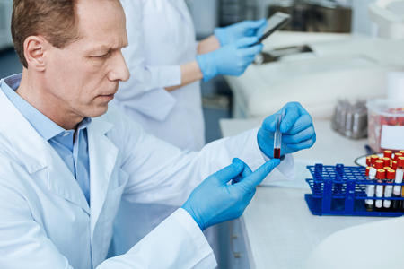genomics: Portrait of serious scientist while looking attentively at test tube