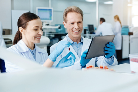 Positive delighted scientific couple looking at screen of the tablet