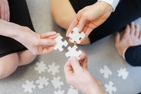 teambuilding: Close up of puzzle pieces being put together