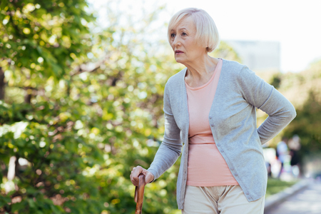 Aged woman walking in the park Stock Photo