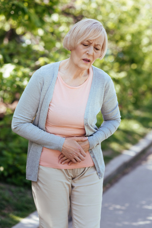 Sad senior woman having pain in the stomach outdoors