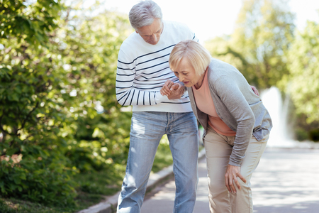 Caring pensioner helping senior wife outdoors