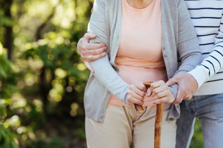 Loving senior man helping aging wife outdoors