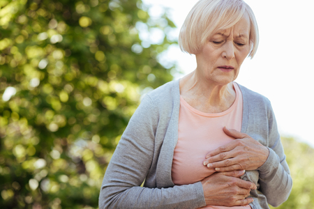 Good looking aged woman having heart attack outdoors