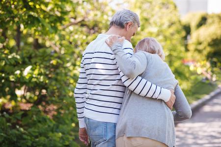 Helpful man helping senior wife in the park