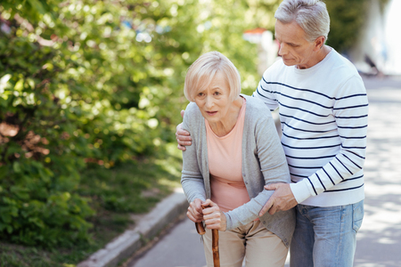 Caring senior husband helping ill wife in the park