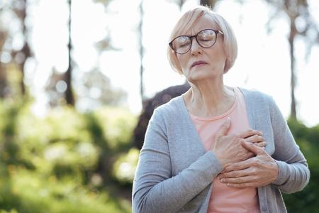 Overwhelmed pensioner having heart attack outdoors