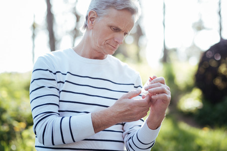 Concentrated pensioner holding bottle with pills outdoors