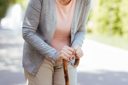 Aged woman leaning on the stick in the park