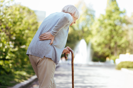 Retired ill woman feeling backache in the park Stock Photo