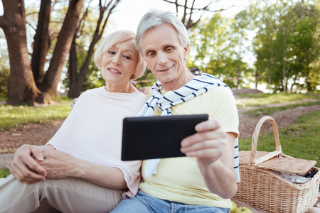 Skilled old couple using electronic device in the park