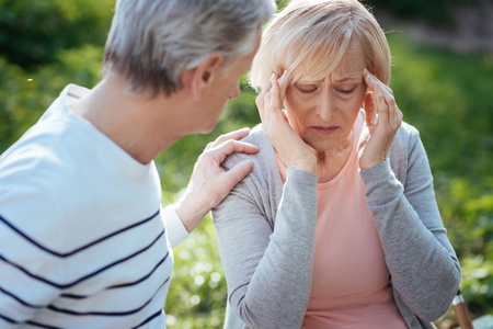 Upset pensioner feeling terrible pain in the head outdoors