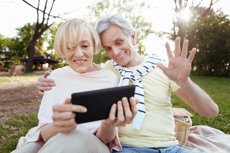 Optimistic old couple using tablet in the park Stock Photo