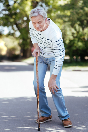 Confused pensioner feeling ache in knee outdoors Stock Photo
