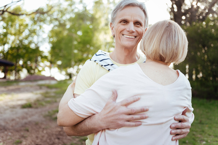 Happy pensioner hugging his wife in the park Stock Photo