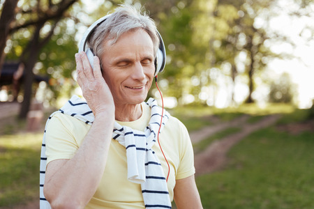 Inspired aging man enjoying music outdoors