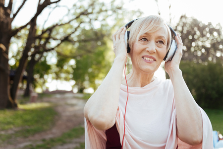 Cheerful aging woman enjoying music in headphones outdoors