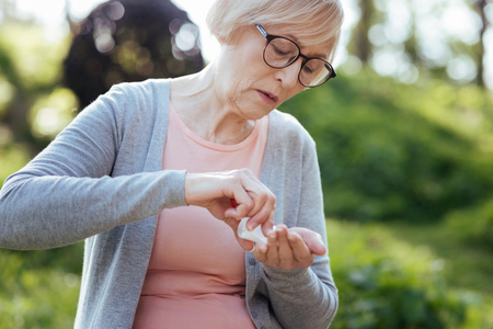 Retired woman taking pills in the park Stock Photo