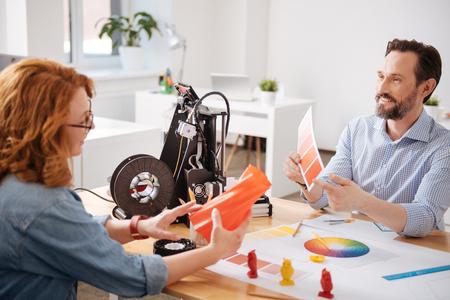 Happy creative designer pointing at the orange colour