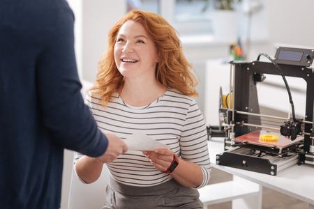 Pleasant good looking woman taking a document Stock Photo
