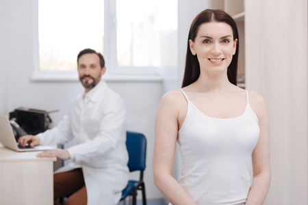 marking up: Enthusiastic graceful woman visiting plastic surgeon for lifting procedure