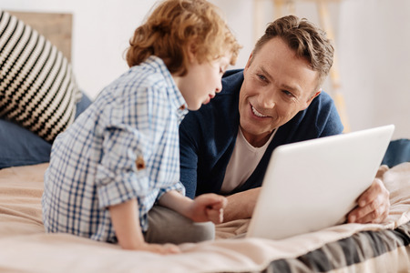 upbringing: Positive delighted father looking at his child Stock Photo