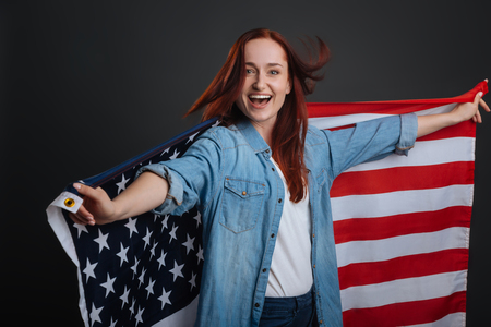patriot act: Enthusiastic happy woman dancing with national flag