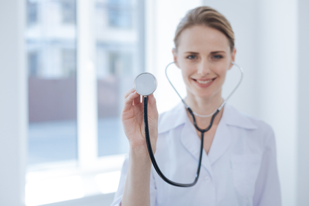 Cheerful physician demonstrating stethoscope in the hospital Stock Photo